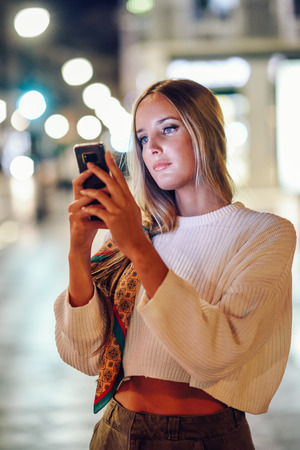 Blonde woman taking photograph with smartphone at night in the street. Defocused city lights at the background. Pretty girl with pigtail hairstyle at night.