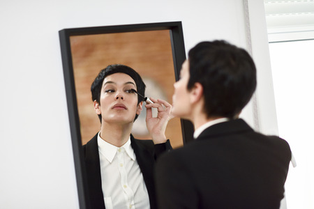 Young woman with very short haircut, putting makeup on in front of the mirror at home. Girl wearing suit with black blazer jacket. 스톡 콘텐츠