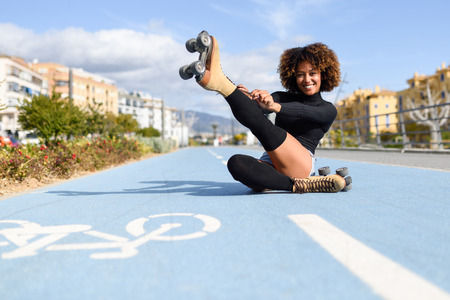 Funny smiling black girl sitting on bike line and puts on skates. Woman with afro hairstyle rollerblading on sunny day