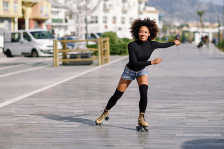 Young fit black woman on roller skates riding outdoors on urban street. Smiling girl with afro hairstyle rollerblading on sunny day Stock Photo