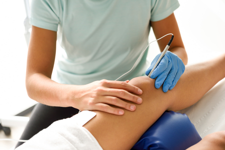 Electroacupuncture dry with needle connecting machine used by acupunturist on female patient for acupuncture guided by EPI Intratissue Percutaneous Electrolisis. Electro stimulation in physical therapy to knee of a young woman in physiotherapy center. Stockfoto