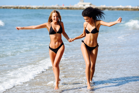 Two young women with beautiful bodies in swimwear on a tropical beach. Funny caucasian and arabic females wearing black bikini walking along the shore holding hands.