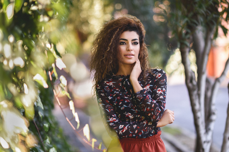 Beautiful young arabic woman with black curly hairstyle. Arab girl wearing casual clothes in the street.