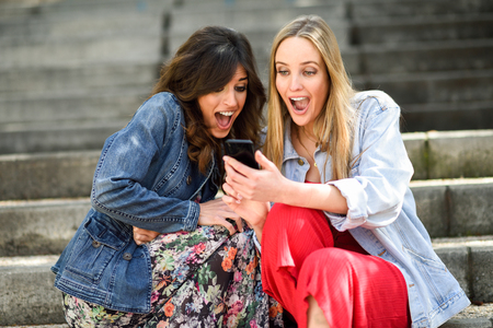 Two young women looking at some awesome thing on their smart phone outdoors, sitting on urban steps. Friends girls.