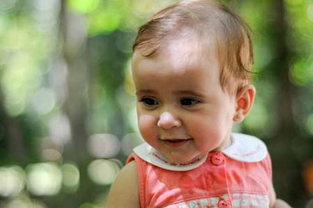 Close-up portrait of six months old baby girl smiling outdoors with defocused background. 写真素材