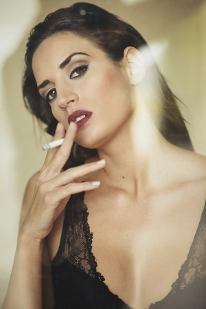Young beautiful brunette woman smoking cigarette on yellow background. Girl wearing black lingerie through a window glass.