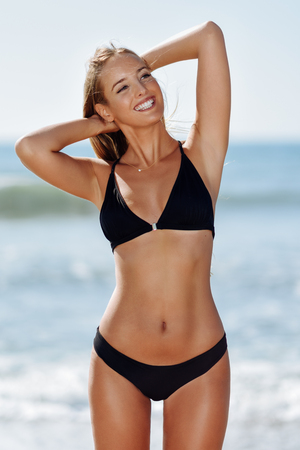 Young blonde woman with beautiful body in swimwear smiling on a tropical beach. Caucasian female with straight long hairstyle wearing black bikini. Stock Photo