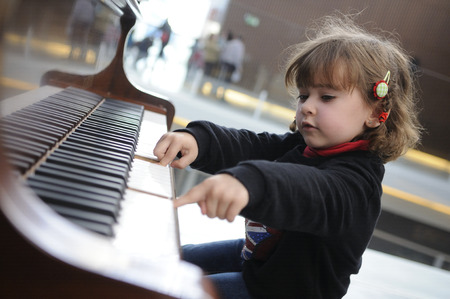 Adorable little girl having fun playing the piano