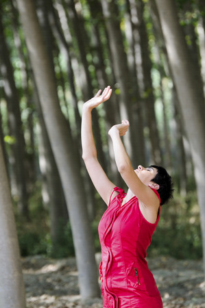 Woman dressed in red, meditating in the forest 版權商用圖片