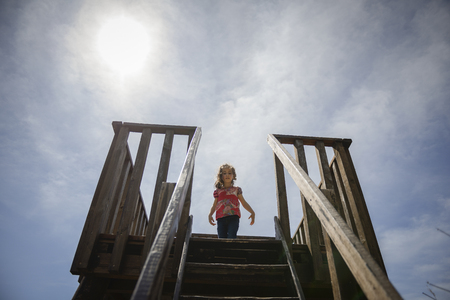 Little girl climbing to a wooden observation tower in a wetland in Padul, Granada, Andalusia, Spain
