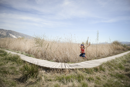 Little girl walking on a path of wooden boards in a wetland in Padul, Granada, Andalusia, Spain Фото со стока