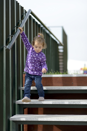 Little 20-month-old girl going down some stairs outdoors Banque d'images - 106992411