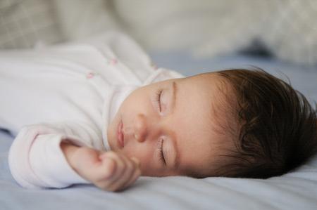 Newborn baby girl sleeping on blue sheets at home 版權商用圖片