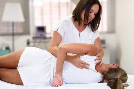 Profesjonalny fizjoterapeuta daje masaż ramion blondynce w szpitalu. Badanie lekarskie barku w centrum fizjoterapii.