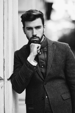 Young bearded man, model of fashion, in urban background wearing british elegant suit. Guy with beard and modern hairstyle in the street.