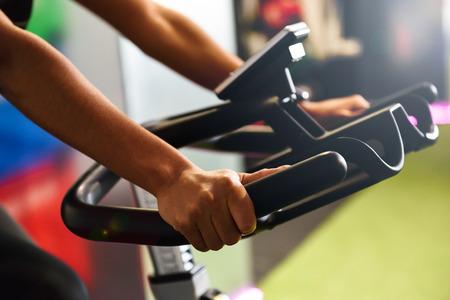 Primo piano delle mani della donna che si allena in una palestra facendo spinning o ciclo indoor. Concetto di sport e fitness. Archivio Fotografico