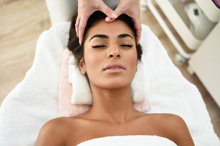 Arab woman receiving head massage in spa wellness center. Beauty and Aesthetic concepts.