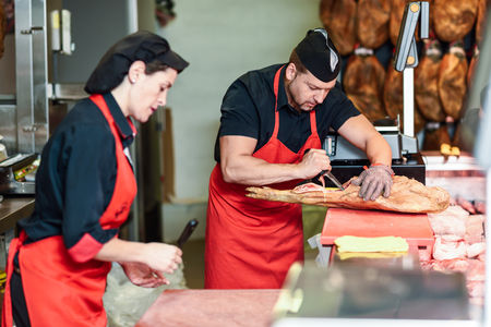 Male and female butchers boning a ham in a modern butcher shop