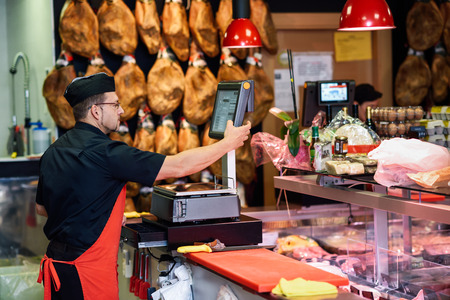 Butcher in a butcher's shop weighing the meat and charging with ham at the background Stok Fotoğraf