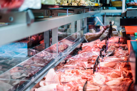 Fresh raw red meat at the butcher in refrigerated display