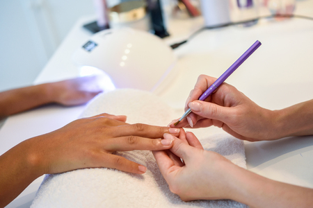 Close-up of beautician painting a womans nails with a brush in a nail salon. Costumer receiving a manicure.