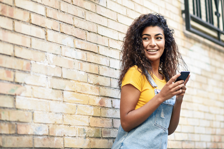 Happy Arab girl using smart phone on brick wall. Smiling woman with curly hairstyle in casual clothes in urban background. Stockfoto