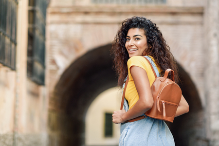 Rear view of young Arab woman with backpack outdoors. Traveler girl in casual clothes in the street. Happy female wearing yellow t-shirt and denim dress in urban background. Фото со стока
