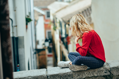 Young blonde tourist woman sitting outdoors looking a beautiful narrow street in Granada, Andalusia, Spain
