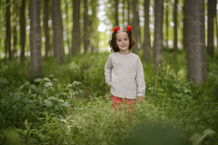 Cute little girl with four years old having fun in a poplar forest 版權商用圖片