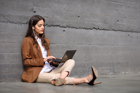 Young businesswoman sitting on floor looking at her laptop computer.