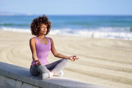 Schwarze Frau, Afro-Frisur, im Lotussitz mit geschlossenen Augen am Strand