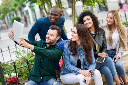 Multi-ethnic young people taking selfie together in urban background
