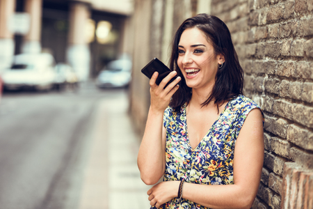 Smiling young woman recording voice note in her smart phone