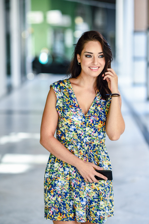 Young woman walking on the street carrying smart phone. Stock Photo