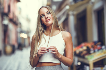 Beautiful young blonde woman in urban background. Stock Photo