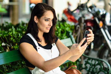 Young woman taking photographs with her smart phone outdoors.