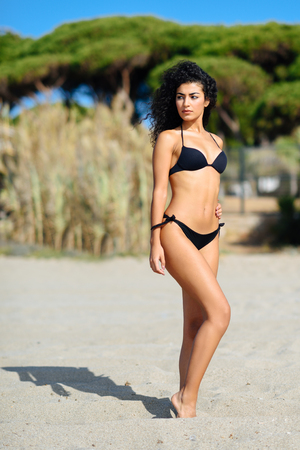 Young arabic woman with beautiful body in swimwear on a tropical beach.