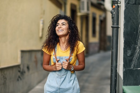 Young North African woman with black curly hairstyle outdoors. Stock Photo
