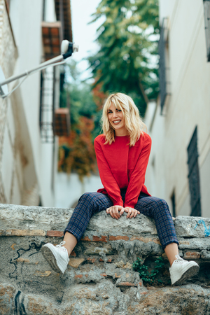 Smiling blonde girl with red shirt enjoying life outdoors. Stock Photo