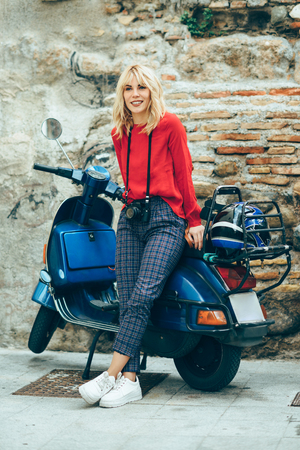 Young blond woman sitting on an old blue scooter wearing red clothes. Stock Photo