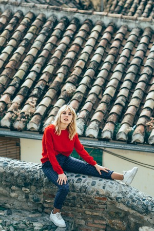 Young blond woman sitting near beautiful roofs of charming old houses.