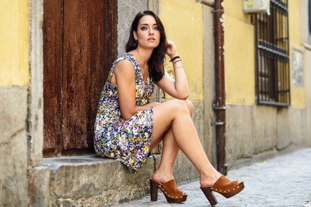 Beautiful young woman with blue eyes sitting on urban step.
