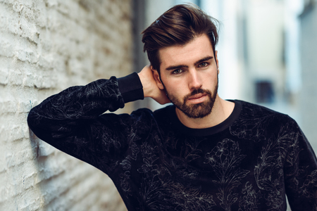 Young bearded man, model of fashion, in urban background wearing casual clothes.