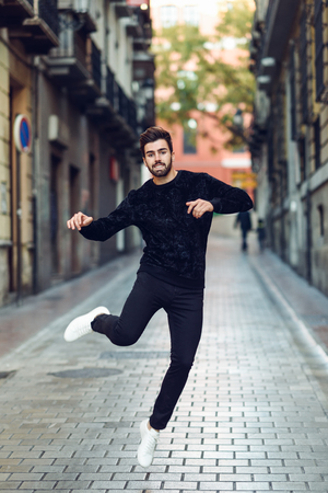 Young bearded man jumping in urban background with open arms wearing casual clothes.