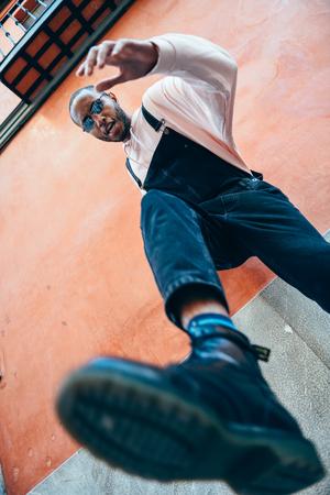 Young black man man kicking towards the ground.