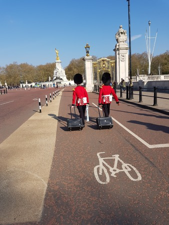 London, United Kingdom, April 14th, 2019. Two men of The Queens Guard coming to buckingham palace with their luggage Editorial