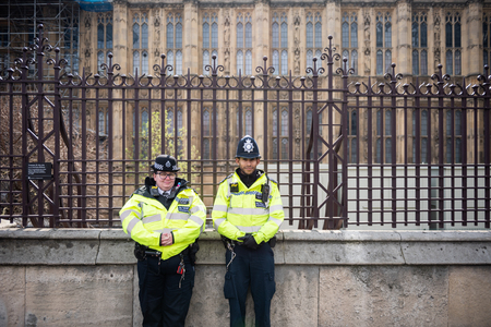 London, United Kingdom, April 13th 2019:- Two police officers, man and woman, standing outside Westminster Parliament.