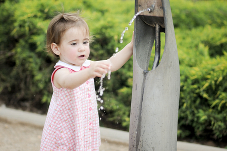 Little girl drinking water in a park fountain