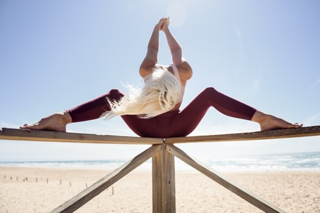 Caucasian woman practicing yoga at seashore. Young female on wooden bridge, Andalusia, Spain. Stock Photo