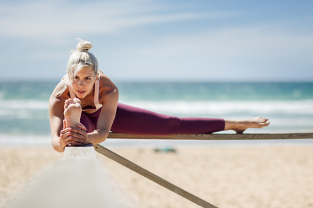 Caucasian woman practicing yoga at seashore. Young female stretching legs in the beach in Cadiz, Andalusia, Spain.
